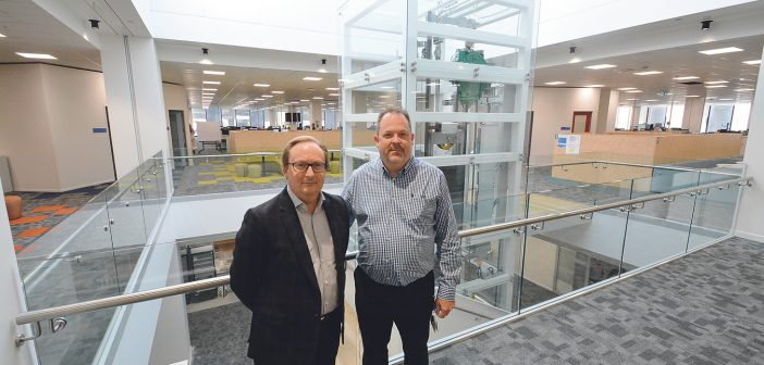 Chris Cardwell and Gary Nelson in the new offices. The staircase and liftwell bring light into the building from a skylight